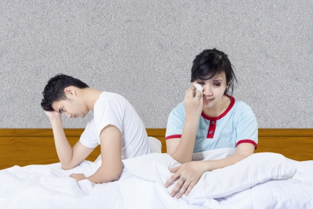 chinese sex:  Crying girlfriend after fight in bed on grey background