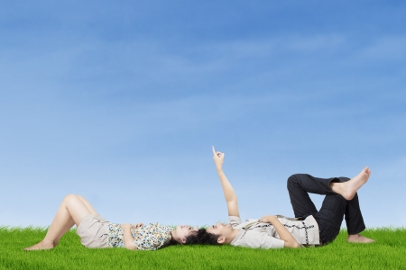 Happy young couple lying on the grass while pointing to copy space in the sky photo