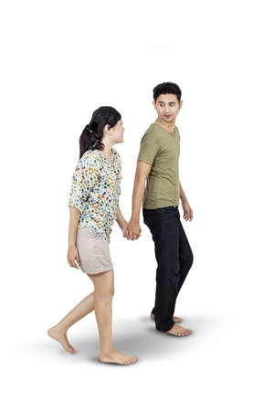 people walking white background: Happy Asian couple walk together