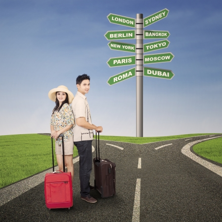 Couple honeymoon travel with luggages and road sign photo