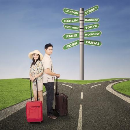 persona viajando: Pareja de viaje de luna de miel con equipaje y se�al de tr�fico Foto de archivo