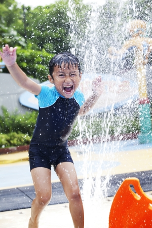 Happy boy play water in waterpark photo