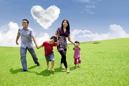 Happy asian family is having a stroll in the park under heart shape clouds photo