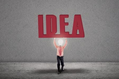 Bright businessman with light bulb head carry IDEA letter Stock Photo - 19225734