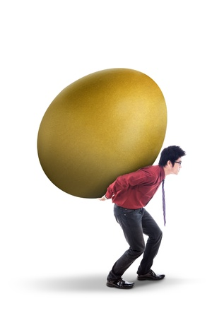 Businessman is carrying golden egg on his back, isolated on white photo