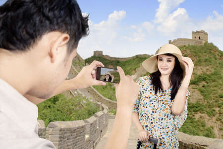 Asian tourist posing in front of the Great Wall China photo