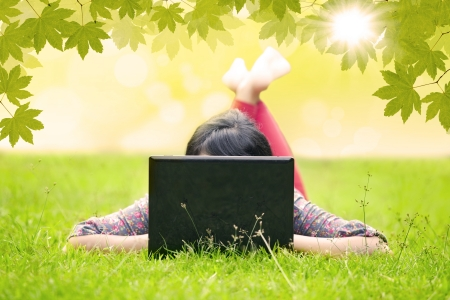 net book: Attractive woman using laptop in the park lying on the green grass