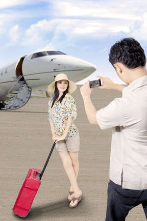 Asian traveller arrive at airport, with her husband took picture of her Stock Photo - 19250389