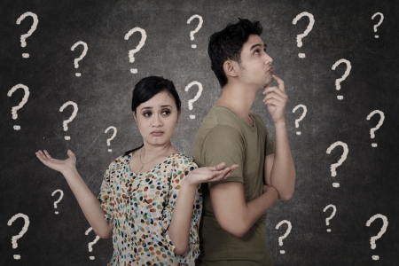 asking question: Confused couple with question marks on blackboard