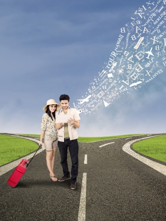 Couple standing on the road looking for holiday destination online photo