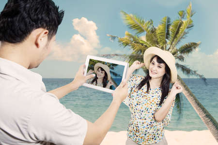 Asian couple take picture at beach in Hawaii photo