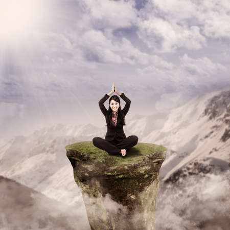 Happy businesswoman is doing yoga meditation on a rock on top of mountain photo