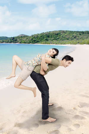 Asian couple having a good time at beautiful beach photo