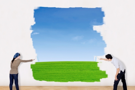 Asian couple paint outdoor field with blue sky and green grass photo