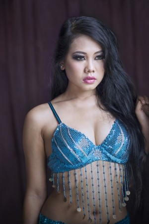 Attractive Asian belly dancer portrait on black background photo