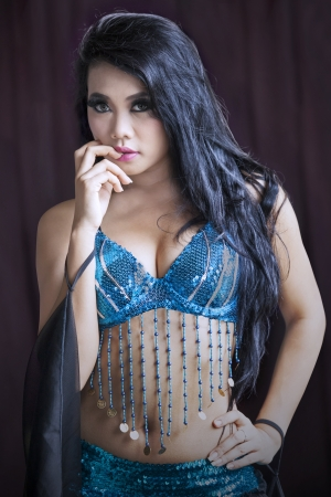 Attractive belly dancer in blue costumer on black background photo