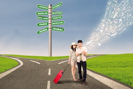 people traveling: Couple is looking for travel direction online at cross road with e-tablet