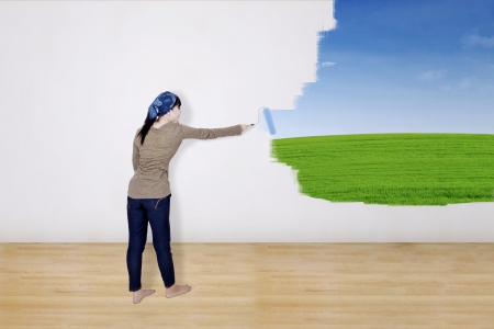 Girl painting green field on wall  photo