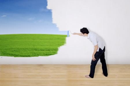 hombre pintando: Novio campo verde pintura en la pared Foto de archivo
