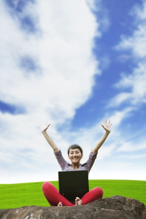 Asian woman raising her hands while using laptop in the park under blue  sky photo