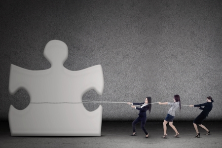 only 3 people: Three businesswomen are pulling a piece of puzzle on grey background Stock Photo