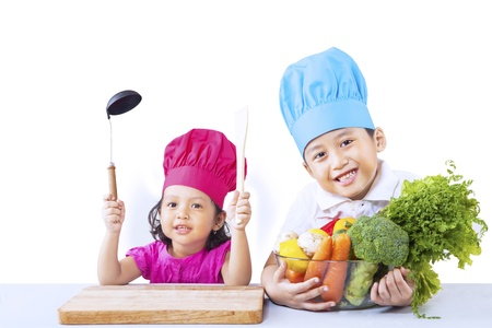 Two little chef ready to cook isolated on white background photo