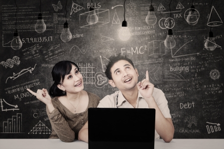 couple lit: Asian students  looking at solution light bulbs in classroom