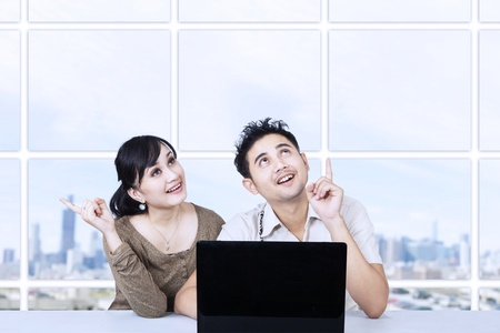asian couple: Asian couple looking up something in office