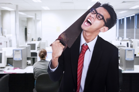 Frustrated businessman cutting his neck with a saw at office photo