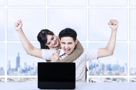 asian couple: Happy couple with laptop in office Stock Photo
