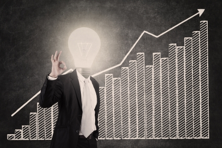 light classroom: Businessman showing OK sign with lightbulb head and profit bar chart