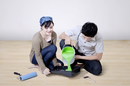 timber floor: Boyfriend pour green paint at home helped by his girlfriend