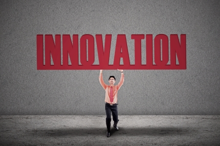 Businessman is holding the word Innovation on grey background photo