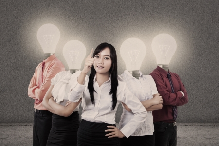 Businesswoman and team with light bulb heads photo