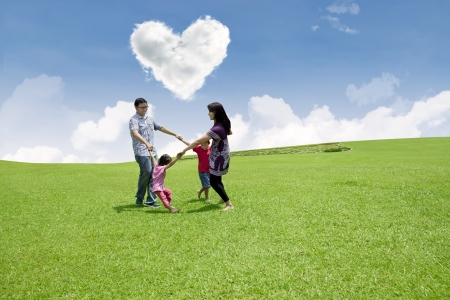under heart: Family dancing under heart shape clouds on green field
