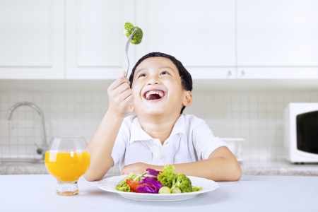 Happy boy eating brocoli with fork in kitchen