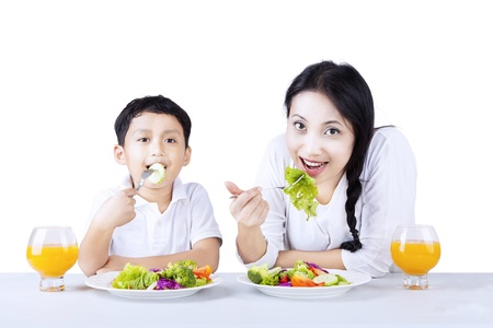 chinese spinach: Beautiful mother and her son are having salad on white background