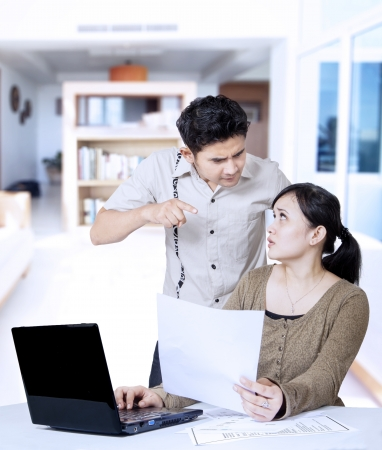 Angry boyfriend pointing at home while girlfriend working with laptop photo