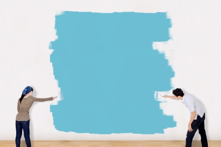 home improvements: Asian couple painting the wall in blue