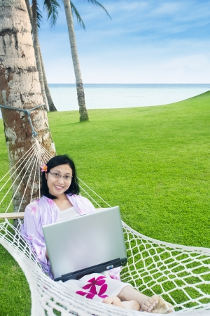 Asian student with laptop on hammock at beach, Indonesia Stock Photo - 19425658