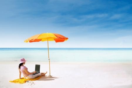 Mulher asiática com chapéu-de-rosa que trabalha na praia em Queensland, Austrália Imagens