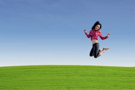 Young asian woman jumping over green field photo