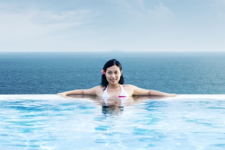 Asian woman relaxing at luxury infinity pool by the beach photo