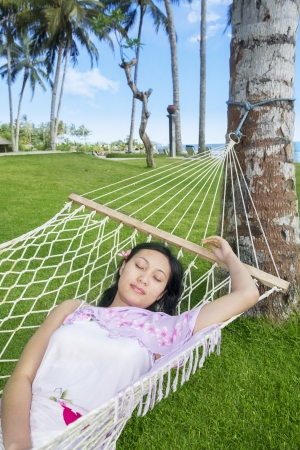 Asian woman sleep in hammock by the beach photo