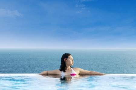 resort life: Attractive Asian woman relaxing at infinity swimming pool