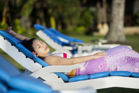 Attractive woman sunbathing at beach resort with sarong in Bali, Indonesia photo