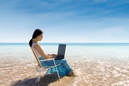 매력적인 여자 해변에서 노트북을 사용하는