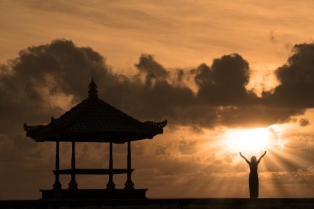 sacred: Silhouette of woman and outdoor pavilion during sunset at Bali beach, Indonesia Stock Photo