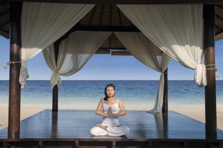 resort: Beautiful yoga woman at luxury beach resort, Indonesia Stock Photo