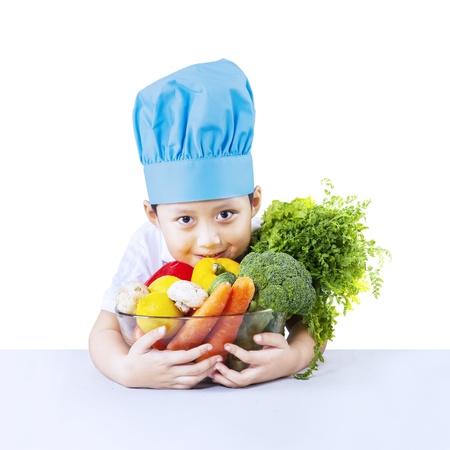 hispanic kids: Boy chef and vegetable isolated on white background